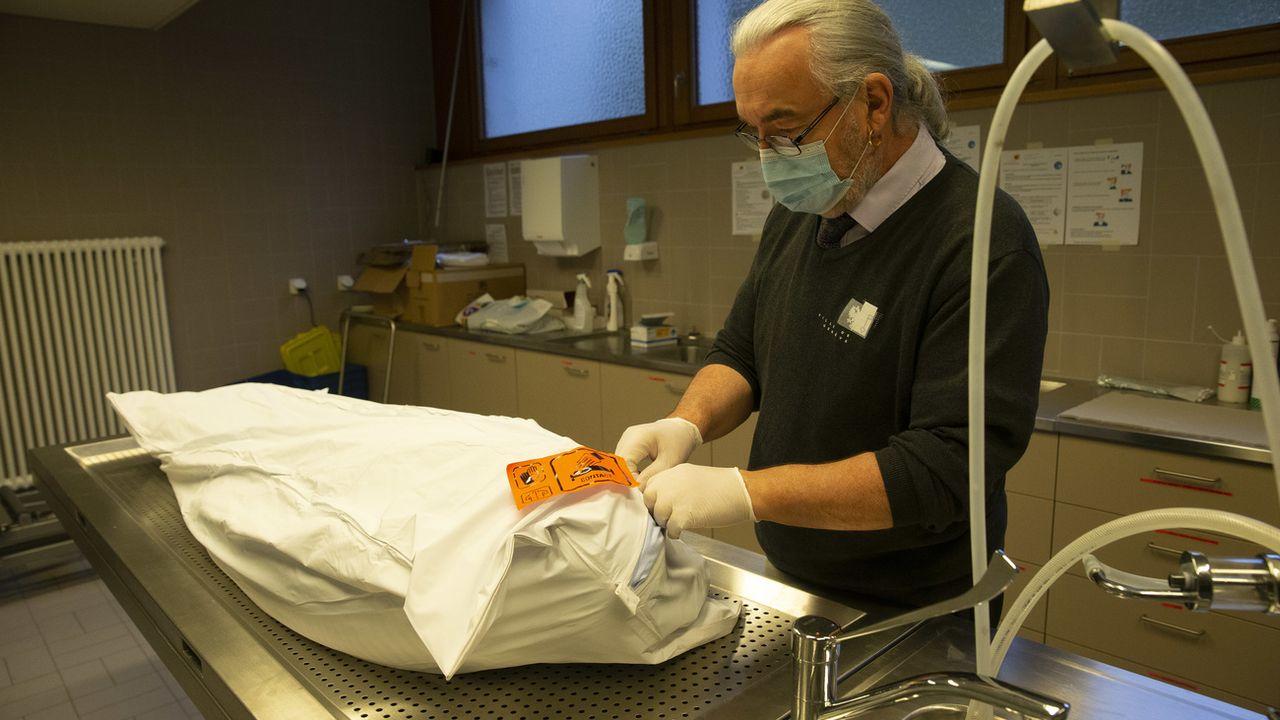 Un employé des pompes funèbres va préparé un corps dans le centre funéraire du cimetière des Rois. [Salvatore Di Nolfi - Keystone]
