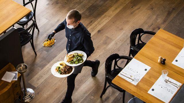 Un serveur au travail dans une brasserie lausannoise au moins de mai 2020. [Jean-Christophe Bott - Keystone]