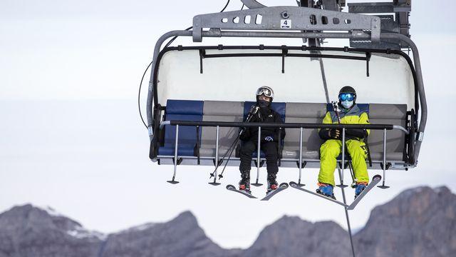 Des skieurs sur un télésiège au Titlis (UR) le 10 novembre 2020. [Alexandra Wey - Keystone]