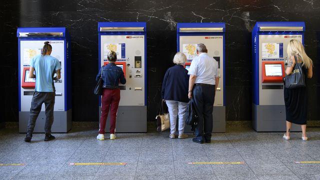 Des personnes achètent des billets à des distributeurs de billets à la gare CFF de Bienne. [KEYSTONE/Anthony Anex - Keystone]