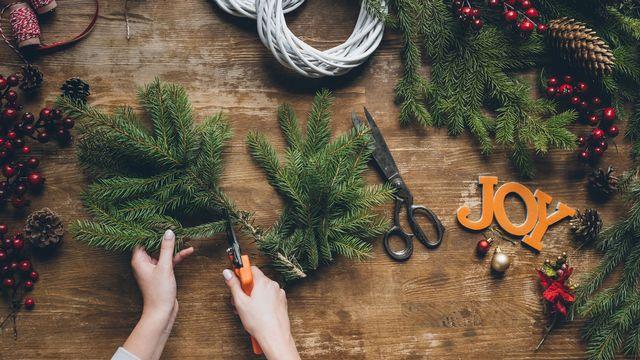 Gros plan sur les mains d'une personne qui fabrique des décorations de Noël. [VadimVasenin - Depositphotos]