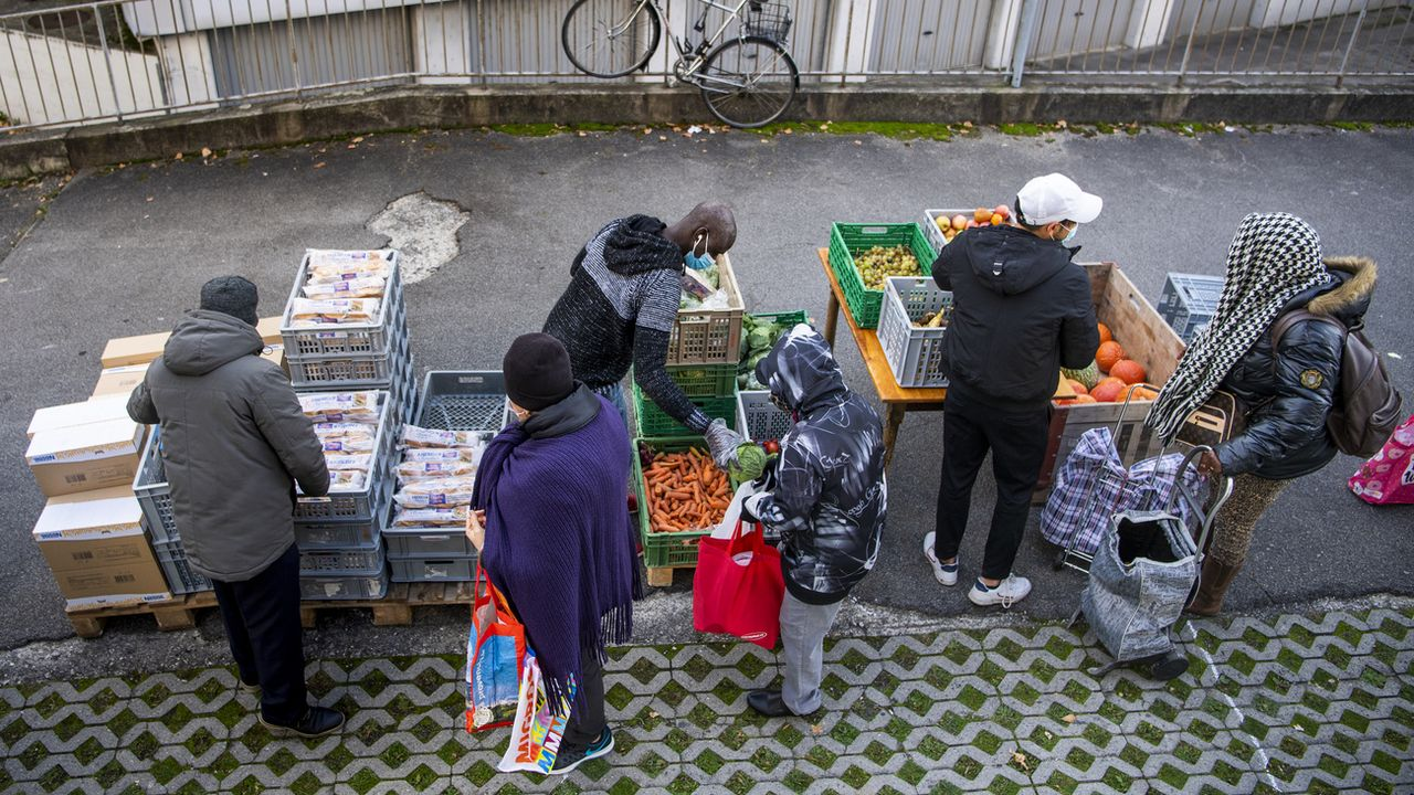 Des bénévoles de l'association Solid-ère distribuent des sacs alimentaires à Lausanne. [Jean-Christophe Bott - Keystone]