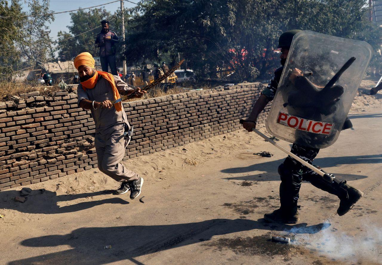 Un policier face à un agriculteur pendant une manifestation le 27 novembre contre les réformes agraires. [Danish Siddiqui - Reuters]