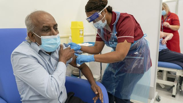 Une dose de vaccin administrée à un patient de 61 ans à Londres. [Dan Charity/Pool via AP - Keystone]