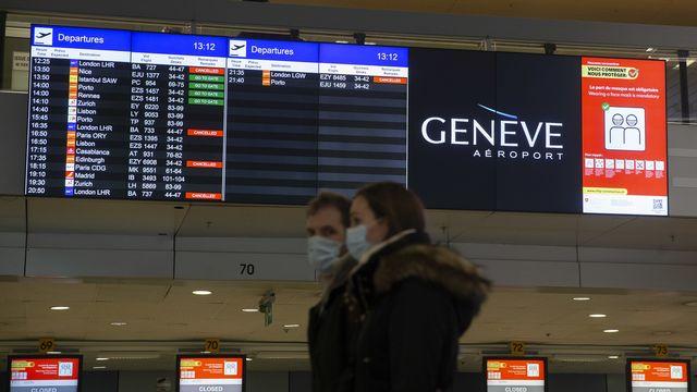 Des passagers à l'aéroport de Genève, devant des annonces de suppression de vols vers et depuis le Royaume-Uni et l'Afrique du Sud. [Salvatore Di Nolfi - Keystone]