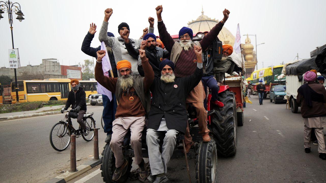 Des fermiers indiens posent sur un tracteur alors qu'ils s'apprêtent à rallier New Dehli. [Raminder Pal Singh - Keystone/EPA]