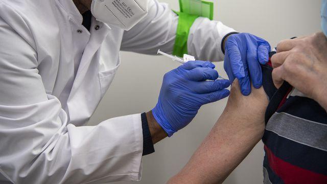 Une personne en train d'être vaccinée à Genève. [Martial Trezzini - KEYSTONE]