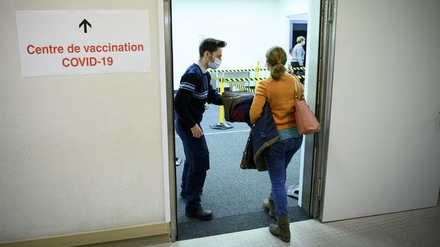 Une personne accueillie par un agent de sécurité à l'entrée du centre de vaccination Covid-19 du CHUV, le 11 janvier 2021 à Lausanne. [Laurent Gillieron - Keystone]