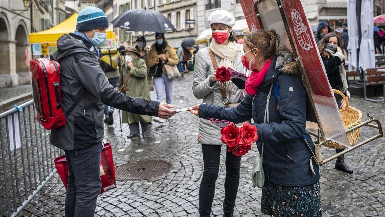La municipale socialiste Florence Germond et la candidate Emilie Moeschler en campagne sur le marché de la Palud à Lausanne, le 12 décembre 2020. [Jean-Christophe Bott - Keystone]