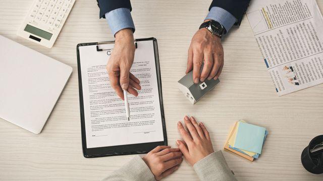 Deux personnes s'apprêtent à signer un contrat de bail. [AndrewLozovyi - Depositphotos]