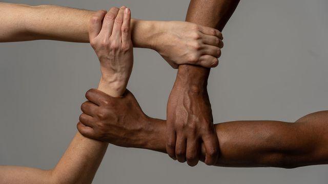 Quatre personnes de couleur de peau différente se tiennent la main. [samwordley@gmail.com - Depositphotos]