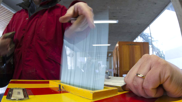Une citoyenne met son bulletin de vote dans l'urne à Carouge (GE), lors des votations fédérales et cantonales du 11 mars 2012. [Salvatore Di Nolfi - Keystone]