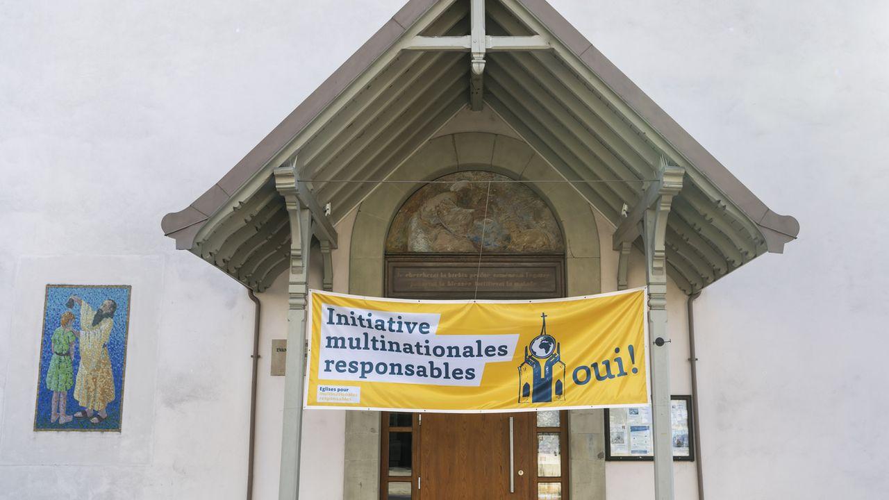 Une banderole en faveur de l'initiative multinationales responsables est visible devant l'église de la paroisse de Morges-Echichens de l'Eglise évangelique réformée vaudoise, à Morges.  [JEAN-CHRISTOPHE BOTT - KEYSTONE]