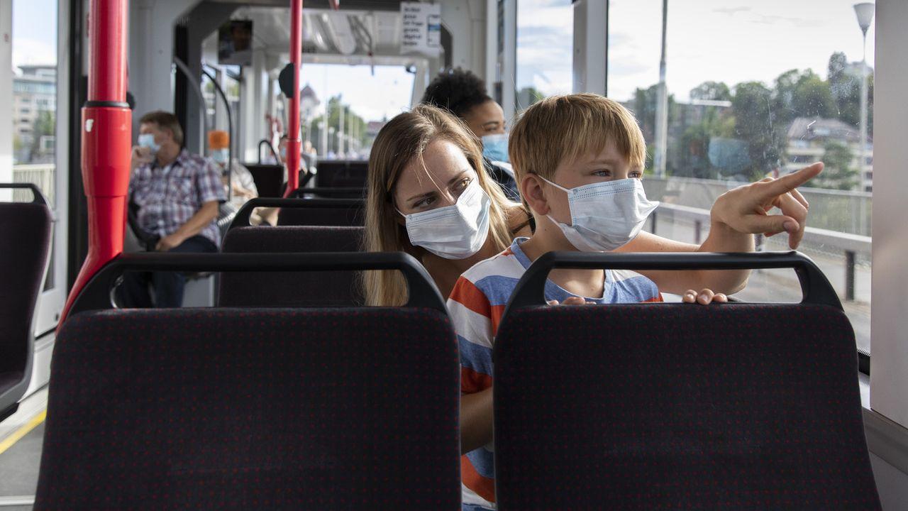 Une femme et un enfants masqués dans le tram à Berne, le 6 juillet 2020. [Peter Klaunzer - Keystone]