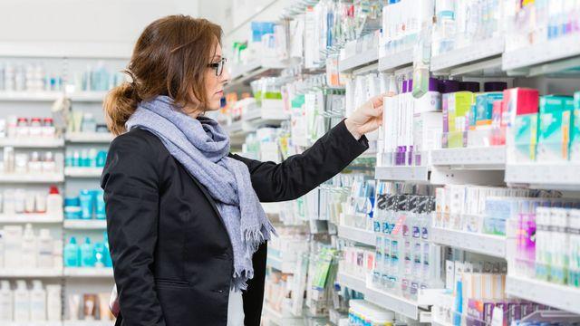 Une femme examine un produit dans les rayons d'une pharmacie. [SimpleFoto - Depositphotos]