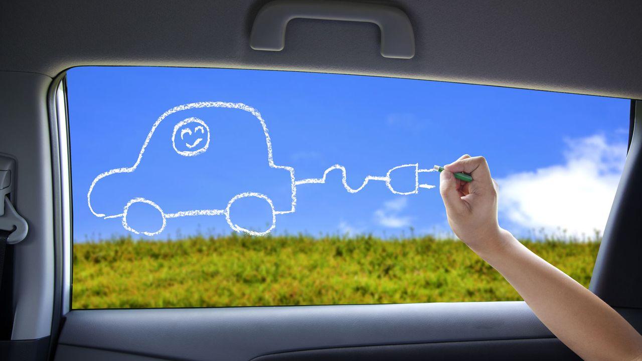 Un enfant dessine une voiture électrique sur la fenêtre d'une voiture. [tomwang - Depositphotos]