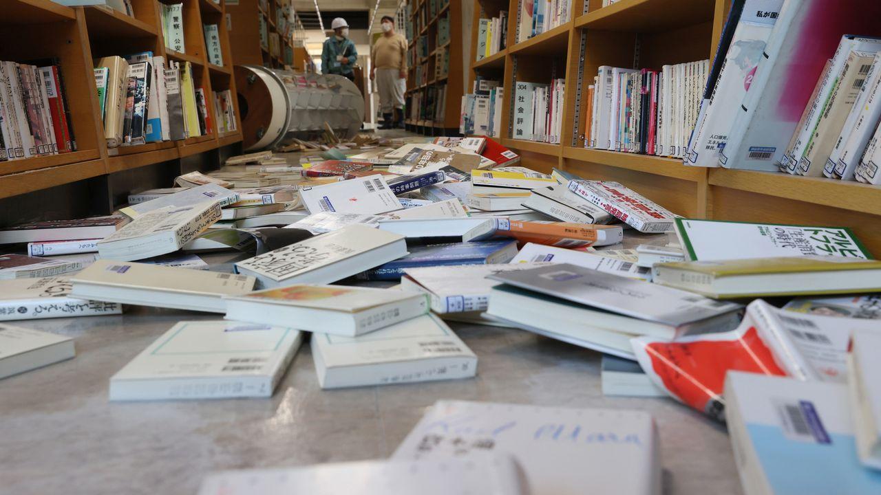 Des livres tombés des rayonnages d'une bibliothèque dans la ville de Koriyama, dans la préfecture de Fukushima ébranlée par un séisme, le 14 février 2021. [Ken Satomi - AFP]
