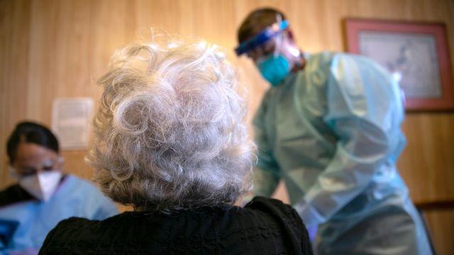 Une personne âgée prise en charge pour une infection au Covid. [John Moore/Getty Images North America - AFP]