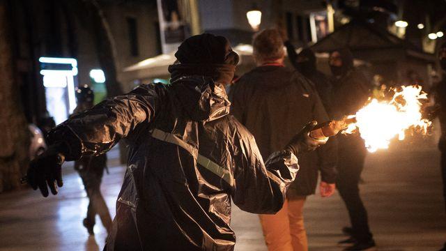 Vitrines brisées, façades taguées et jets de cocktail Molotov lors de la manif du 27.02.2021 à Barcelone. [Emilio Morenatti - AP/Keystone]