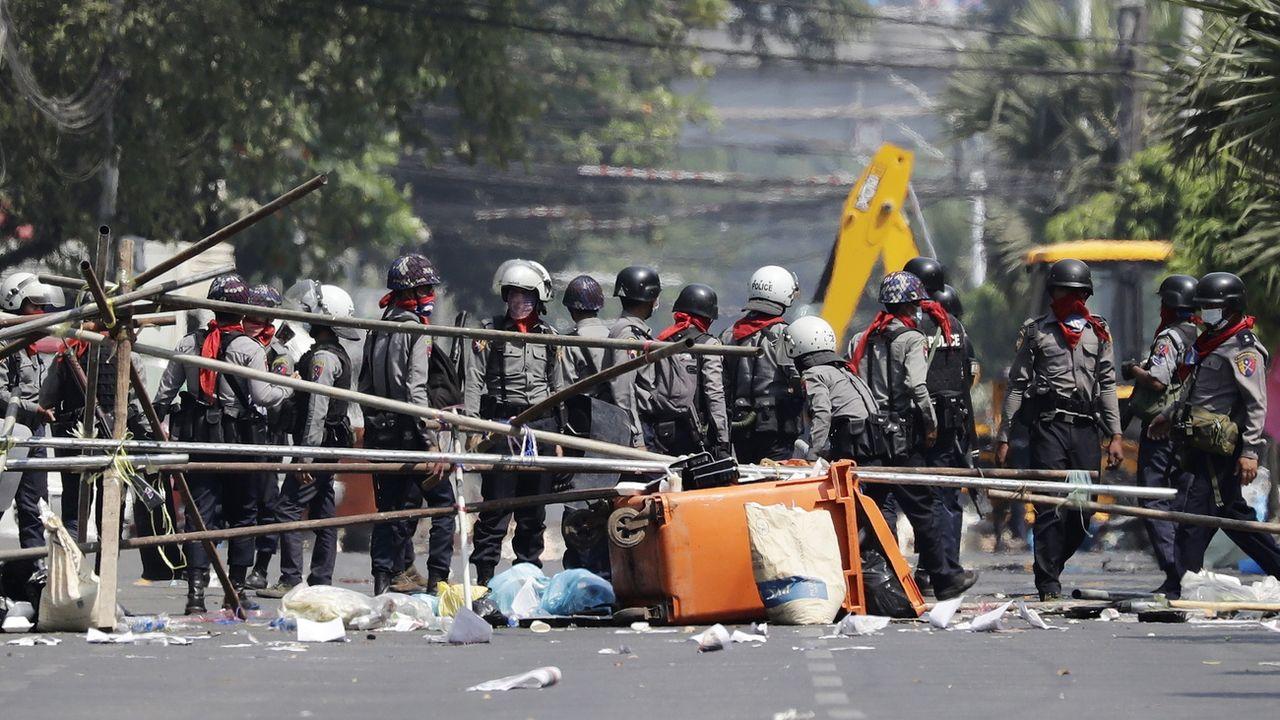 Policiers démontant une barricade à Rangoun, dimanche 28.02.2021. [Lynn Bo Bo - EPA/Keystone]