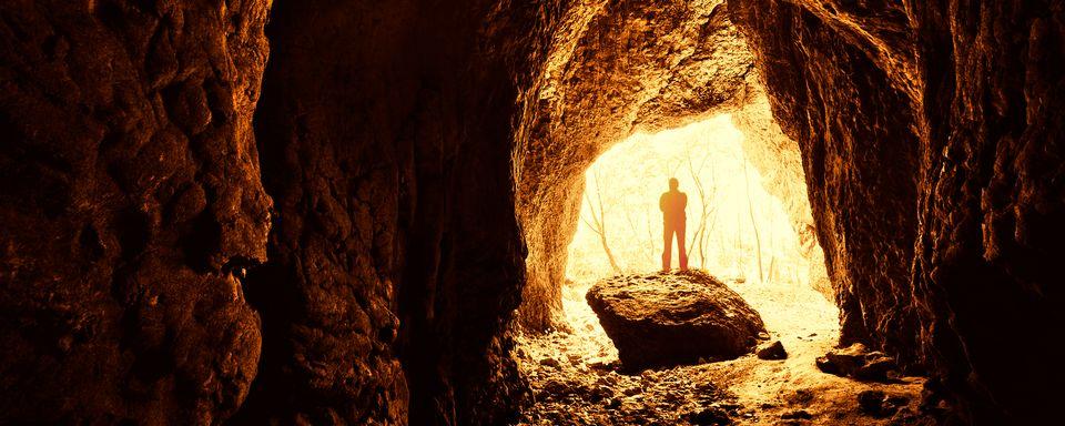 Homme debout devant une entrée de grotte. [photocosma - depositphotos]