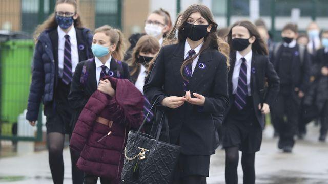 """Des élèves affluent dans leur établissement scolaire le 8 mars 2021, jour de la """"rentrée"""" des écoles au Royaume-Uni, après un troisième confinement. [Danny Lawson - AP/Keystone]"""