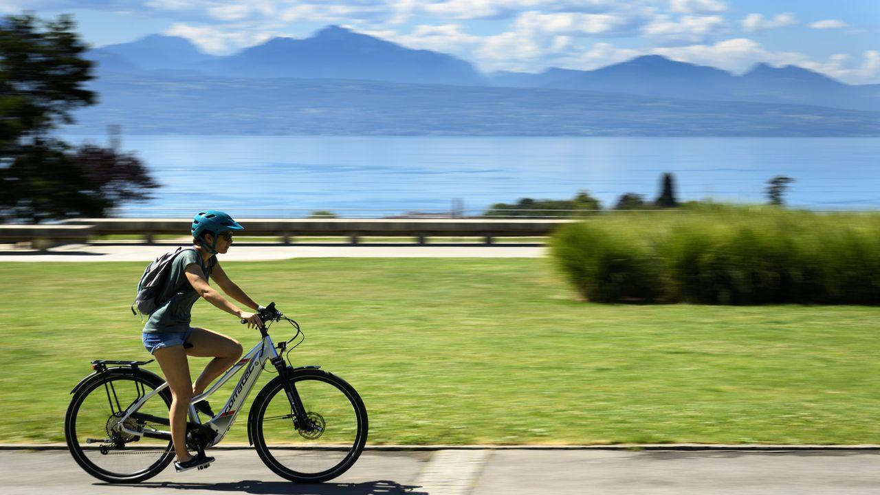 Une personne à vélo électrique sur l'esplanade de Montbenon à Lausanne. [Laurent Gillieron - Keystone]