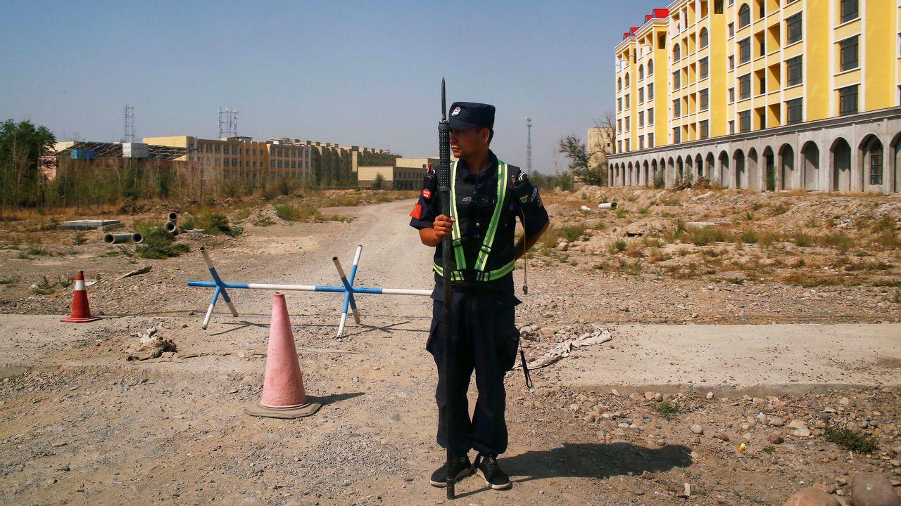 """Un policier chinois garde une route près d'un """"centre de formation professionnelle"""" dans le Xinjiang. [Thomas Peter - Reuters]"""