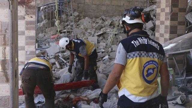 Des Casques blancs à la recherche de victimes sous les décombres d'un bâtiment détruit. [Syrian Civil Defense White Helmets - AP/Keystone]