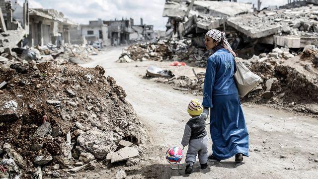 Une femme kurde de Syrie avec son enfant dans les ruines de la ville de Kobane, en mars 2015. [YASIN AKGUL - AFP]