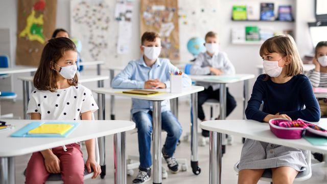 Des enfants qui portent un masque chirurgical sont assis dans une classe. [halfpoint - Depositphotos]