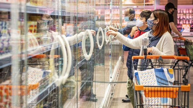 Une femme et son fils choisissent des produits dans un rayon de la Migros. [Urs Flueeler - Depositphotos]