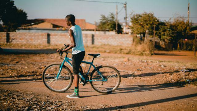 Une jeune homme africain pousse un vélo. [Rachel Martin - Unsplash]