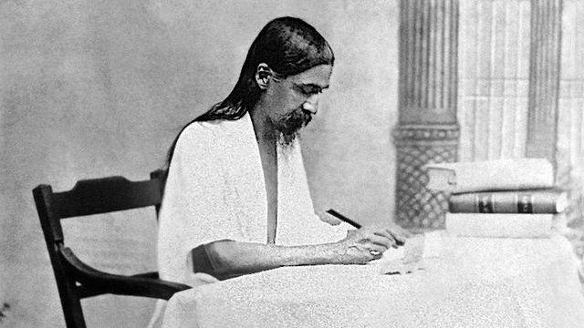 Sri Aurobindo écrivant à son bureau vers 1918-1920. [Public Domain]