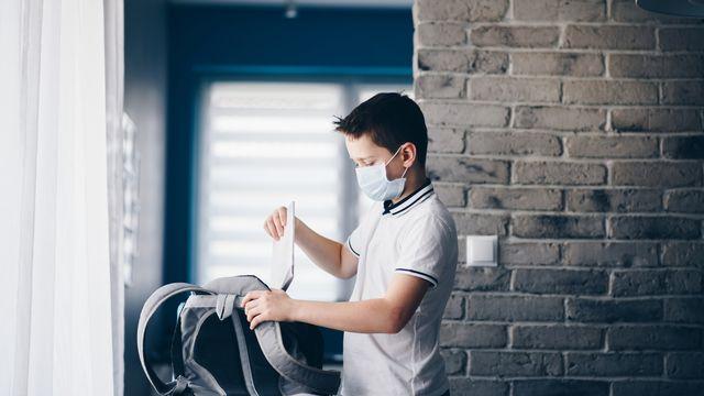 Enfant mis en quarantaine emballant ses livres dans un sac à dos. [djedzura - depositphotos]