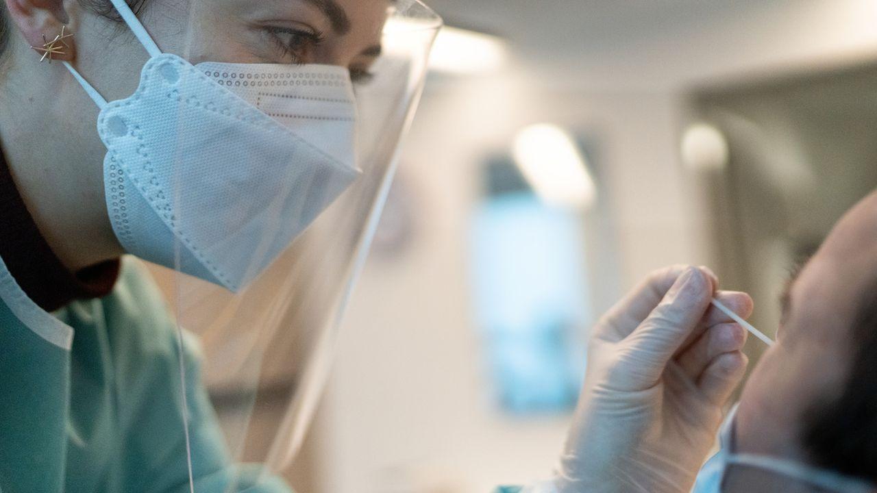 Une pharmacienne en tenue de protection adéquate fait un prélèvement pour un test rapide de l'antigène Covid-19 à Zurich en novembre 2020. [Gaetan Bally - Keystone]