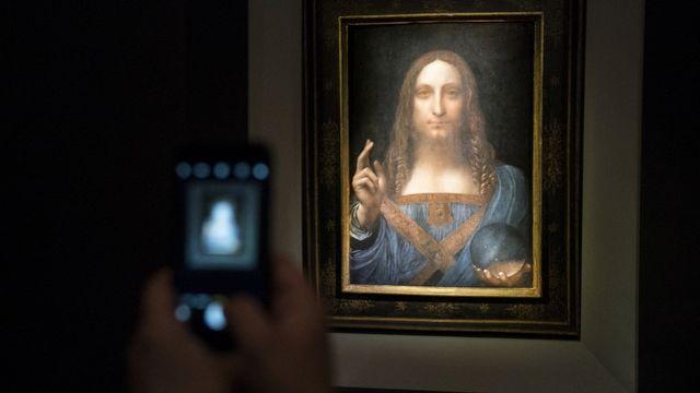 """Le """"Salvator Mundi"""" attribué à Léonard de Vinci lors de sa vente aux enchères à New York, le 15 novembre 2017. [Drew Angerer / GETTY IMAGES NORTH AMERICA - AFP]"""