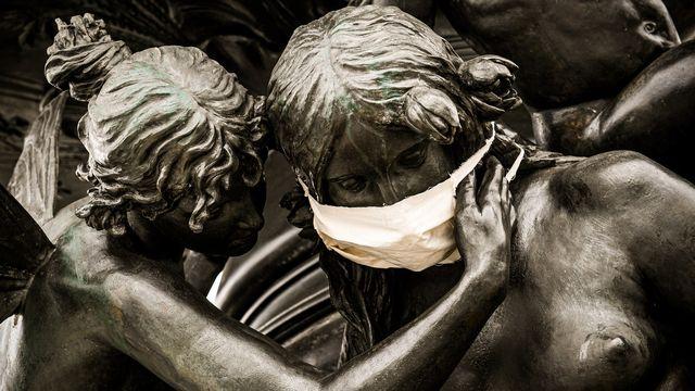 Une statue de bronze porte un masque à Dresden, en Allemagne, le 29 mars 2020. [FILIP SINGER - Keystone]