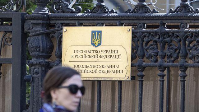 Une femme passe devant l'ambassade ukrainienne à Moscou. [EPA/Sergei Ilnitsky - Keystone]
