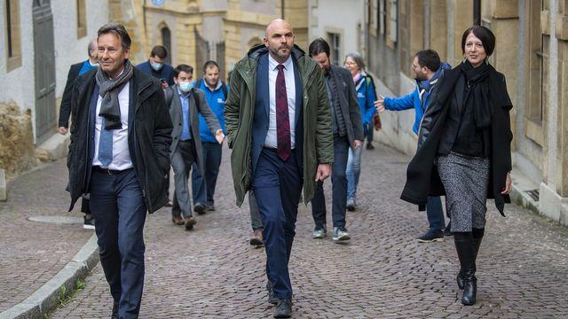Les PLR Alain Ribaux, Laurent Favre et Crystel Graf arrivent au Château de Neuchâtel après leur succès lors de l'élection au Conseil d'Etat. [Jean-Christophe Bott - Keystone]