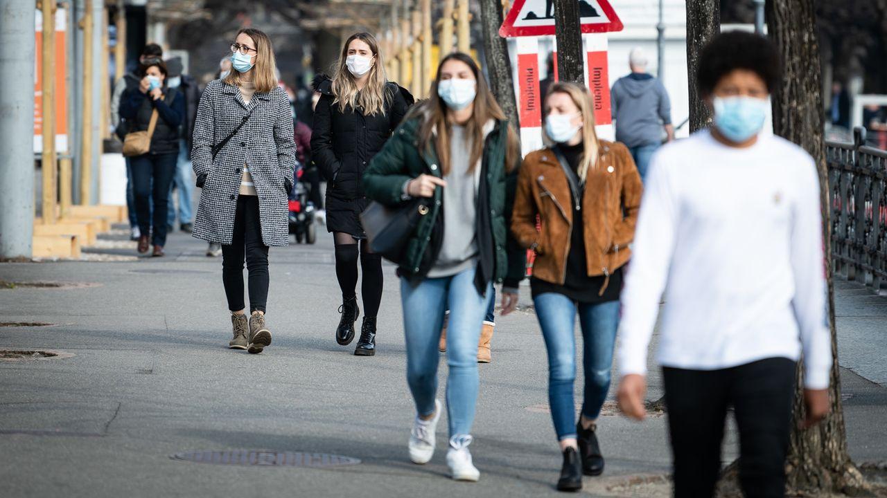 Des personnes portent un masque dans les rues de Lugano. [Ti-Press/Elia Bianchi - Keystone]