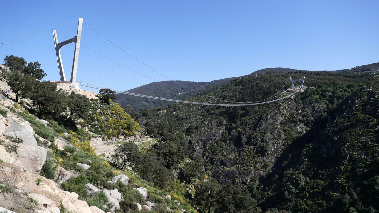A 175 mètres au-dessus de la rivière Paiva, le pont pédestre suspendu le plus long du monde s'est ouvert jeudi dans le nord du Portugal. [EPA/Estela Silva - Keystone]