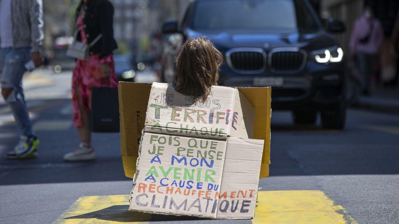 Un militant d'Extinction Rebellion (XR) assis sur la route face à une voiture à Genève. [Salvatore Di Nolfi - Keystone]