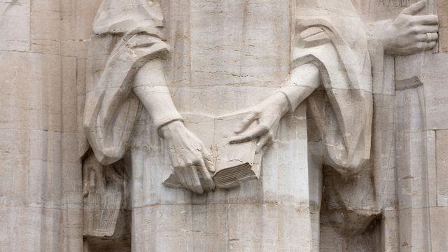 Les mains de Jean Calvin et sa Bible sur le Mur des Réformateurs, dans le parc des Bastions, à Genève. [Gaetan Bally - Keystone]