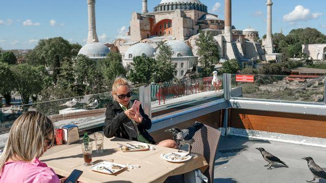 Des touristes devant Sainte-Sophie à Istanbul. [Bulent Kilic - afp]