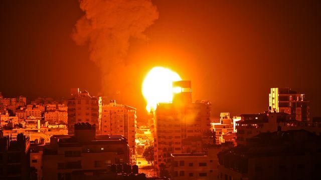 Fumée et boule de feu s'élèvent des points d'impact de roquettes lancées par Israël sur la ville de Gaza, pendant la nuit du 16 au 17 mai 2021. [Mahmud Hams - AFP]