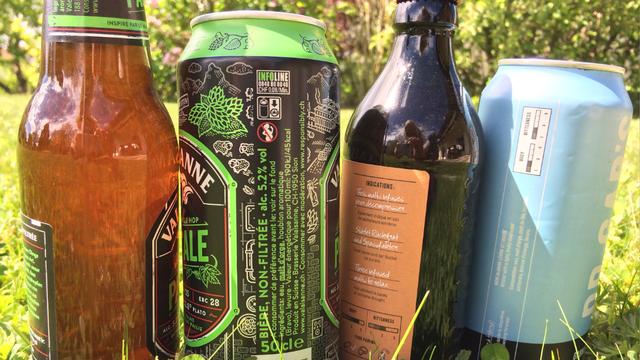 Canettes et bouteilles de bière alignées sur l'herbe. [Frédérique Volery - RTS]
