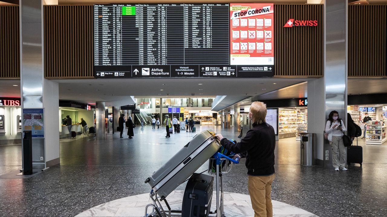 Un homme regarde le tableau des départ dans l'aéroport de Zurich le 1er avril 2021. [Alexandra Wey - Keystone]