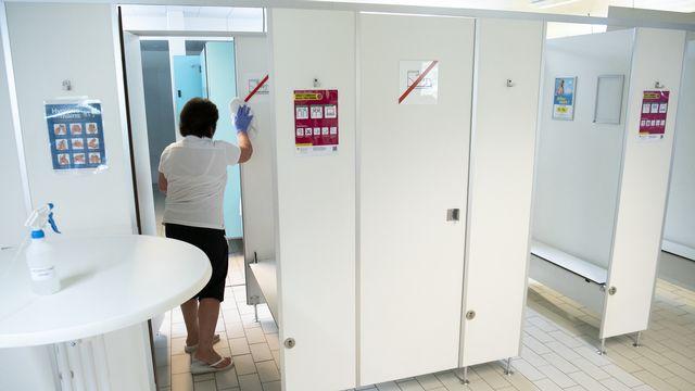 Une employée des Bains de Saillon nettoie une cabine, après la réouverture temporaire de l'établissement, le 6 juin 2020. [Laurent Gillieron - Keystone]