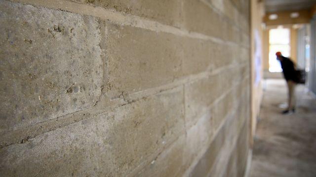 Construction d'un bâtiment avec des matériaux alternatifs: de la brique de terre comprimée. [Laurent Gillieron - Keystone]